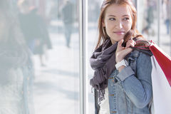 Woman carrying shopping bags while standing by store stock photo