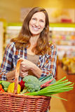 Woman carrying shopping basket Stock Photography
