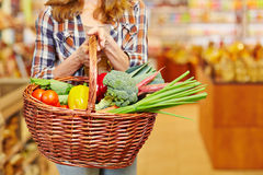 Woman carrying shopping basket in supermarket. Woman carrying shopping basket full of vegetables in a supermarket Stock Image