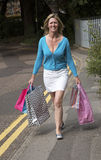 Woman carrying shopping carrier bags Royalty Free Stock Images