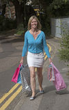 Woman carrying shopping carrier bags Royalty Free Stock Image
