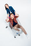 Woman carrying shopping cart with happy man showing thumbs up. Young women carrying shopping cart with happy men showing thumbs up Royalty Free Stock Image