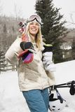 Woman carrying ski equipment. Royalty Free Stock Photography