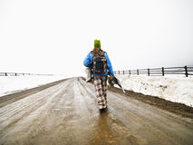 Woman carrying snowboard. Royalty Free Stock Photography