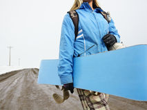 Woman carrying snowboard. Stock Photography
