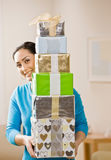 Woman carrying stack of festive birthday gifts stock image