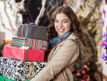 Woman Carrying Stacked Christmas Gifts In Store Royalty Free Stock Photos