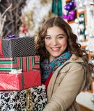 Woman Carrying Stacked Christmas Presents In Store Royalty Free Stock Photography