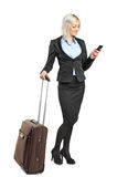Woman carrying a suitcase and writing a sms Royalty Free Stock Photography