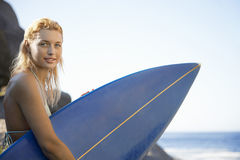 Woman Carrying Surfboard By Ocean Royalty Free Stock Image
