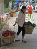 Woman is carrying two backets with cherries and grapes Royalty Free Stock Photos