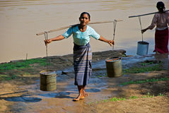 Woman carrying water Stock Images
