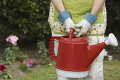 Woman Carrying Watering Can Stock Photography