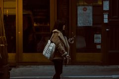 Woman Carrying White Tote Standing Beside Brown Glass Door Building Royalty Free Stock Photos