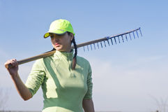 Woman carrying wooden rake Stock Photos