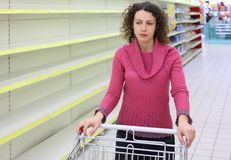 Woman with cart in shop with empty shelves royalty free stock photos
