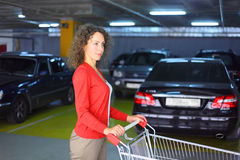 Woman with cart standing in parking Stock Images