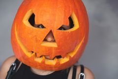 Woman with carved pumpkin on her head for Halloween stock photos