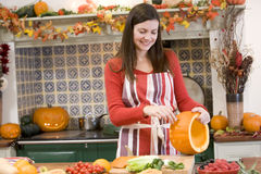 Woman carving jack o lantern on Halloween stock photos