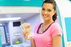 Woman cash ATM. Happy young woman withdrawing or depositing cash at an ATM Stock Photography