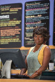 Woman at Cash Register. Beautiful cafe worker at cash register indoors Royalty Free Stock Image