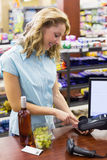 Woman at cash register paying with credit card Stock Photography