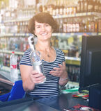Woman at cashdesk with bottle of alcohol Stock Photography