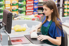 Woman cashier beeping an item. On a grocery royalty free stock photos