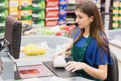 Woman cashier beeping an item Royalty Free Stock Photos
