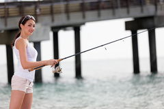 Woman casting a fishing pole Royalty Free Stock Images