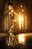 Woman in castle. Woman with carnaval mask in golden evening dress in castle Royalty Free Stock Photos