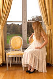 Woman castle window park. Blond girl dressed in a white victorian dress sitting on antique chair looking out of the window with curtains with view on the park Royalty Free Stock Image