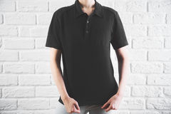 Woman in casual black shirt front. Front view of young woman in casual black shirt. Retail concept. White brick wall background Royalty Free Stock Photo