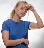 Woman in casual blue shirt with headache stock images