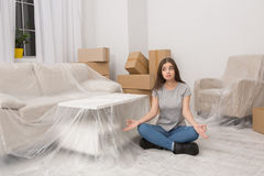 Woman in casual clothes sitting on the floor relaxing after unpacking thigs during the relocation. Stock Photography
