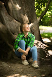 Woman in casual clothes sitting under big tree at forest Royalty Free Stock Photography