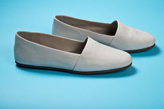 Woman casual gray leather shoes. On blue Royalty Free Stock Image