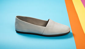 Woman casual gray leather shoes. On blue Stock Photography