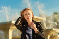 Woman casual style posing against city fountain Stock Photos