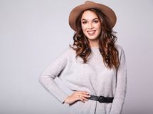 Woman in casual summer clothes with natural makeup posing in studio. Portrait of young stylish laughing girl model in gray casual summer clothes in brown hat Royalty Free Stock Photo