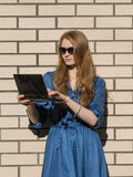 Woman in casual wear leans against white brick wall. Red hair girl is standing outside an office, holding a tablet Stock Image