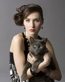 Woman With Cat. Studio photo of elegant young woman holding gray cat Royalty Free Stock Photo