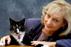 Woman with cat. Mature woman smiling, with cat royalty free stock image