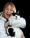 Woman and cat enjoying a laugh. A woman holding her cat and both are enjoing a good laugh , backlit and shot infront of a black background Royalty Free Stock Photography