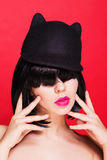 Woman in cat hat. Cap with animal ears. on red Royalty Free Stock Photo