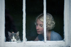 Woman and Cat Looking at the Rainy Weather By the Window. Frame royalty free stock photo