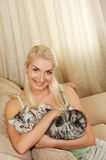 Woman with cat stitting on sofa Royalty Free Stock Image