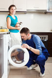 Woman with cat  watching as worker repairing washing machine Stock Photography
