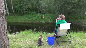 Woman catch carp in rural pond. Hungry cat wait for fish stock footage