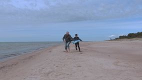 Woman catch man on the beach.Happy couple stock footage